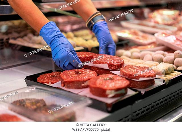 Woman at market stall preparing minced meat