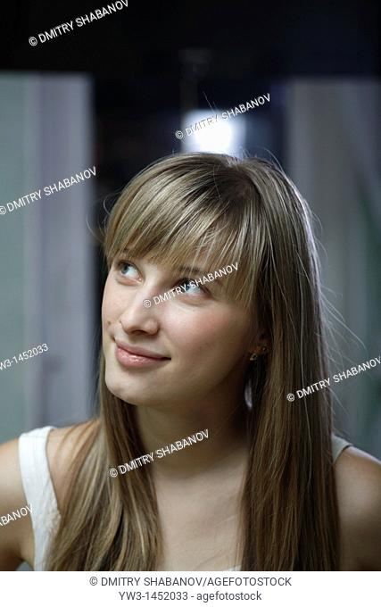 Headshot of a 24 year old blonde Caucasian woman wearing a tank top indoors