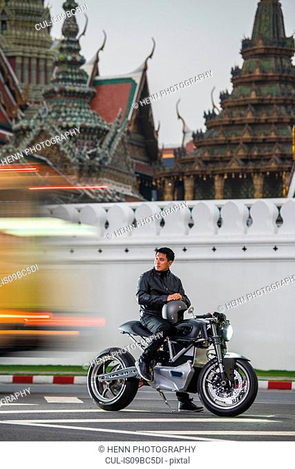 Man with electric motorbike by royal palace, Bangkok, Thailand