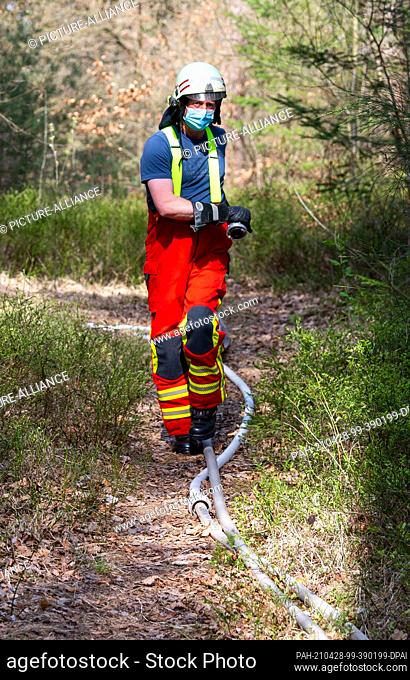 28 April 2021, Lower Saxony, Melbeck: A firefighter lays hoses at a forest fire. By chance, emergency vehicles of the federal police had passed by after an...