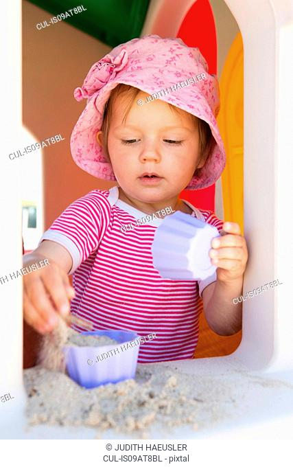 Female toddler playing with sand on playhouse windowsill