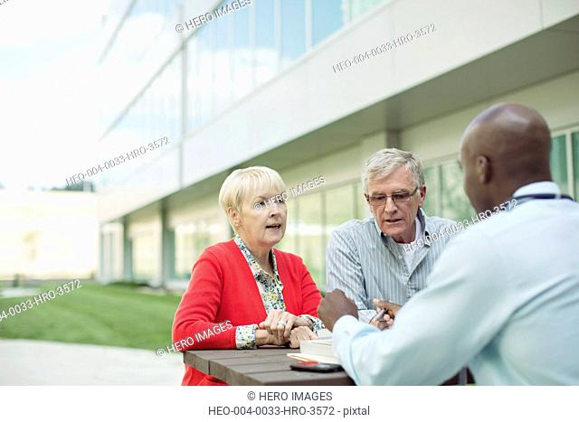 senior couple consulting with dcotor at outdoor table
