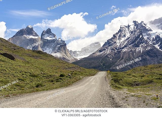 Dirt road with Paine Horns and Cerro Paine in summer. Torres del Paine National Park, Ultima Esperanza province, Magallanes region, Chile