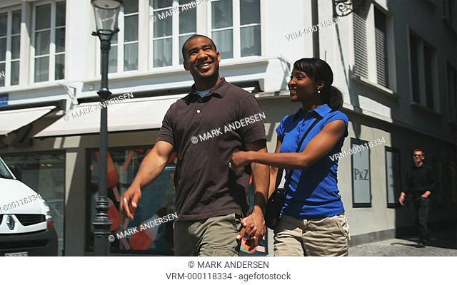 couple walking down a European street holding hands