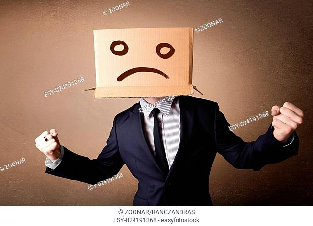 Businessman gesturing with cardboard box on his head with sad face