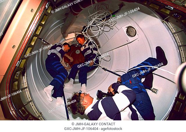 Three STS-88 crew members are pictured in one of two Pressurized Mating Adapters (PMA) connected to the Unity and Zarya modules