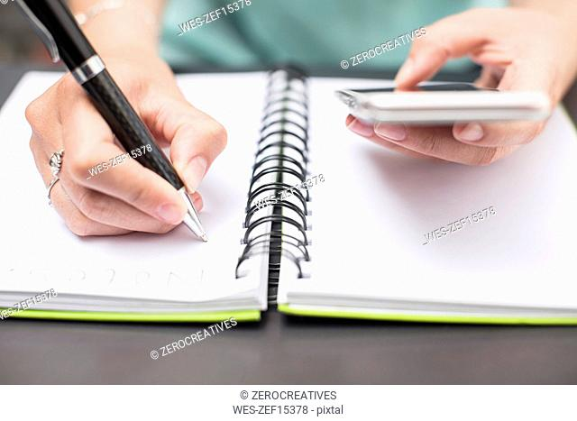 Woman writing notes in diary, holding smartphone