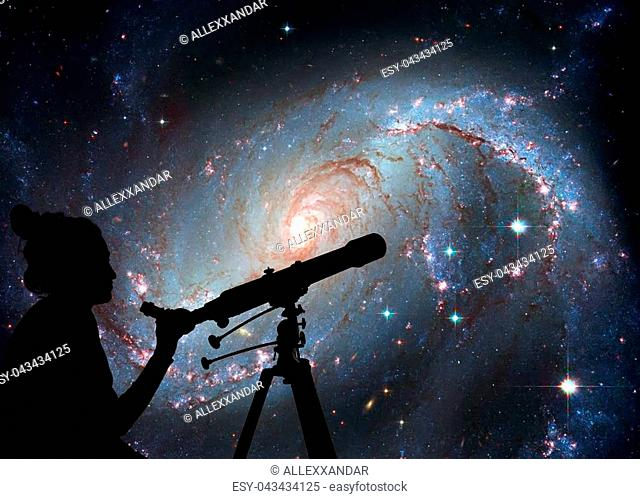 Girl looking at the stars with telescope. Stellar Nursery NGC 1672. Spiral galaxy in the constellation DoradoElements of this image are furnished by NASA