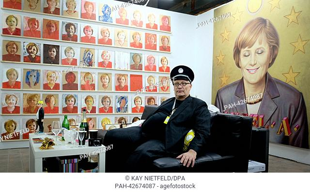 Curator and artist Konstantin Schneider sits in front of artworks with German Chancellor Merkel at the Kraftwerk in Berlin, Germany, 18 September 2013