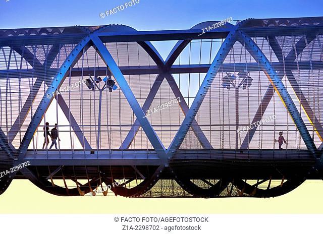 People passing by the Arganzuela bridge, designed by architect Dominique Perrault. Madrid Rio Park. Madrid. Spain