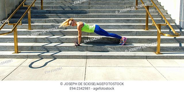 39 year old blond woman wearing fitness clothing doing push ups on the steps of a building in an urban settiing