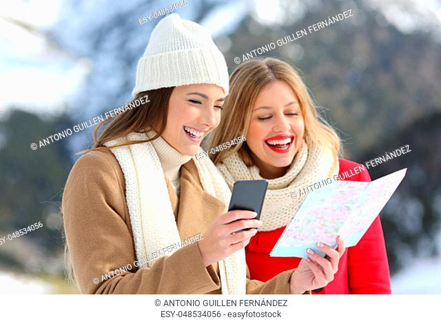 Two happy tourists reading a paper map in winter holidays in a snowy mountain