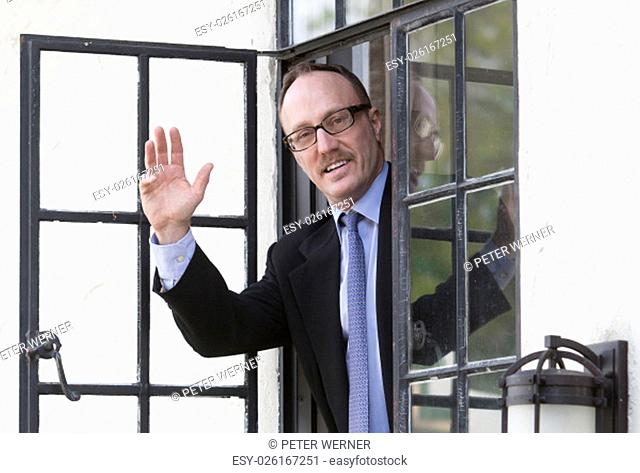 businessman looking out of a window and waves his hand