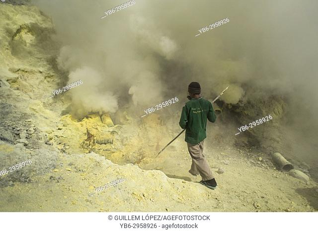 A miner extract sulfur rocks from the Kawah Ijen crater in East Java, Indonesia
