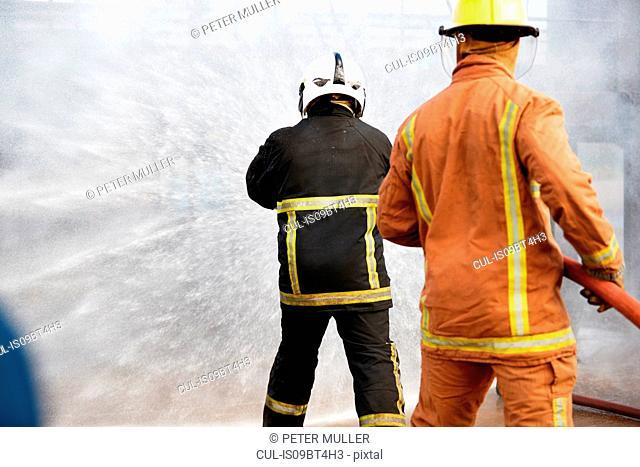 Firemen training, firemen spraying water at training facility, rear view
