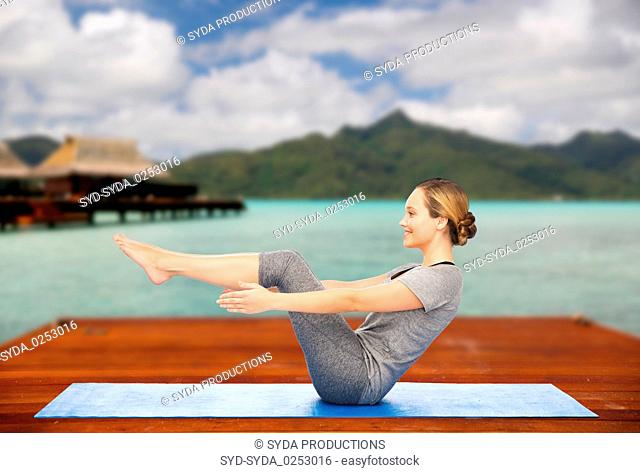 woman making yoga half-boat pose on mat outdoors