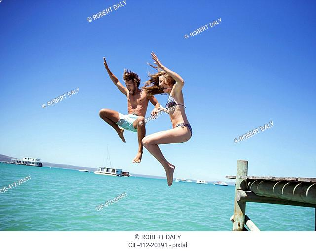Couple jumping off wooden dock together