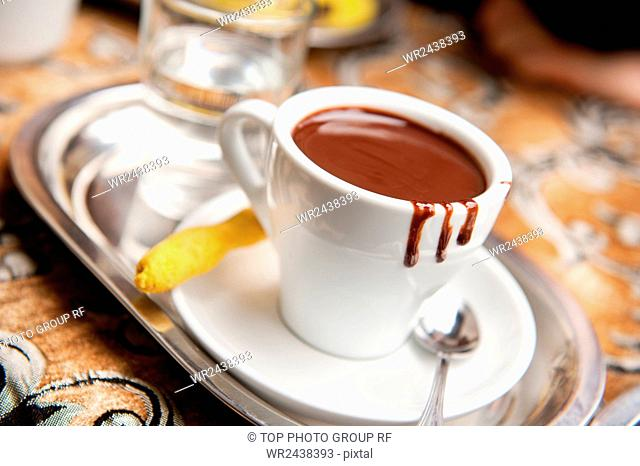 One white ceramic cup with hot milk chocolate and ginger cookie on saucer with glass of fresh mineral water on silver tray, drink on table in Poland