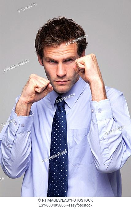 Businessman in shirt and tie with his fists raised ready for a fight
