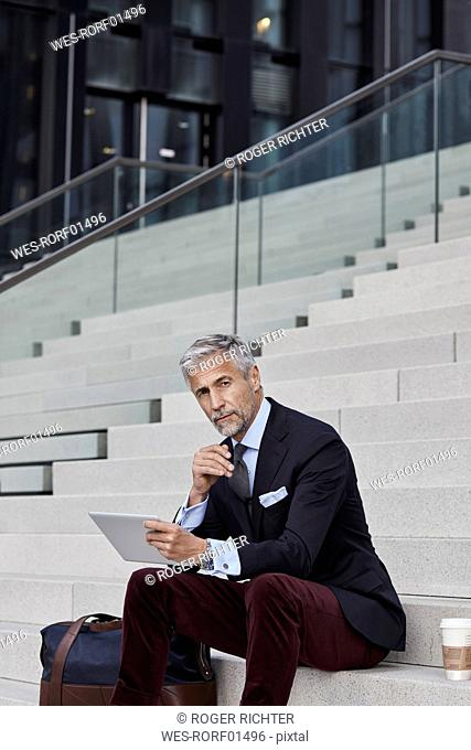Portrait of fashionable businessman with travelling bag, coffee to go and tablet sitting on stairs