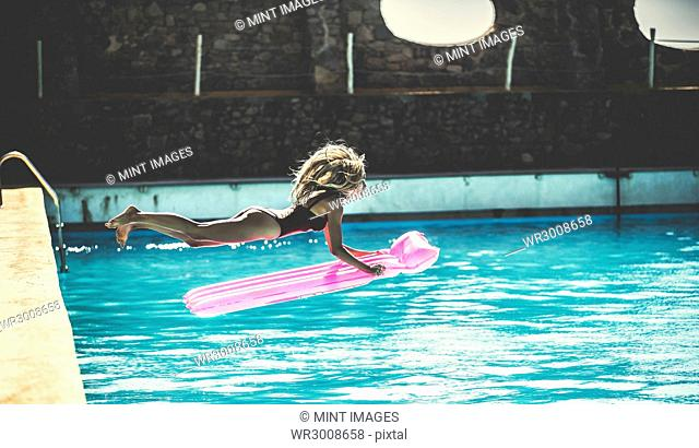 A young woman wearing a swimsuit jumping into a swimming pool holding a pool raft