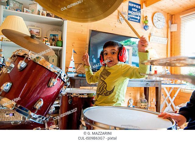 Boy wearing ear defenders playing drums
