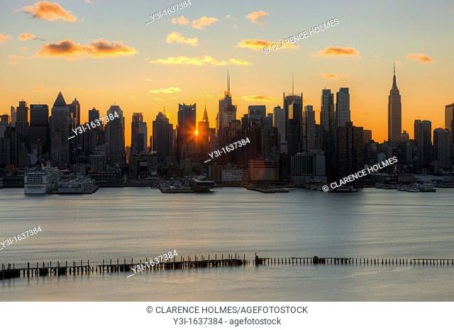 The rising sun shines through the buildings of the Manhattan skyline in New York City a few minutes after sunrise as viewed over the Hudson River looking east...