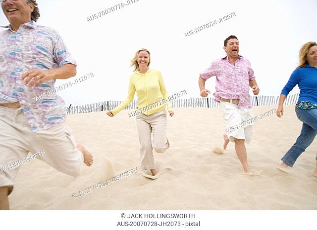 Two couples running on the beach