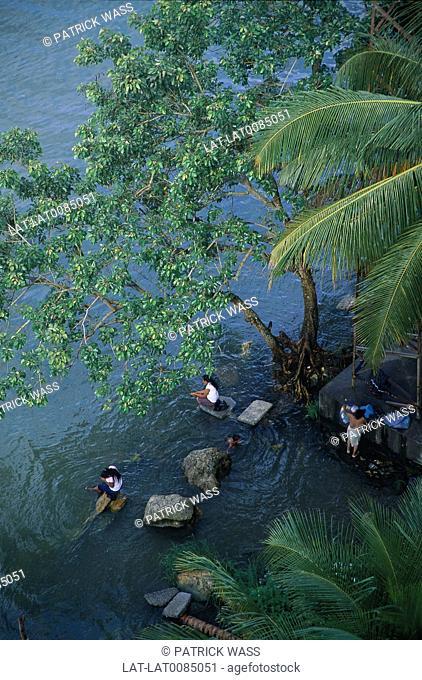 River. Shallows below bridge. Women sitting washing in water