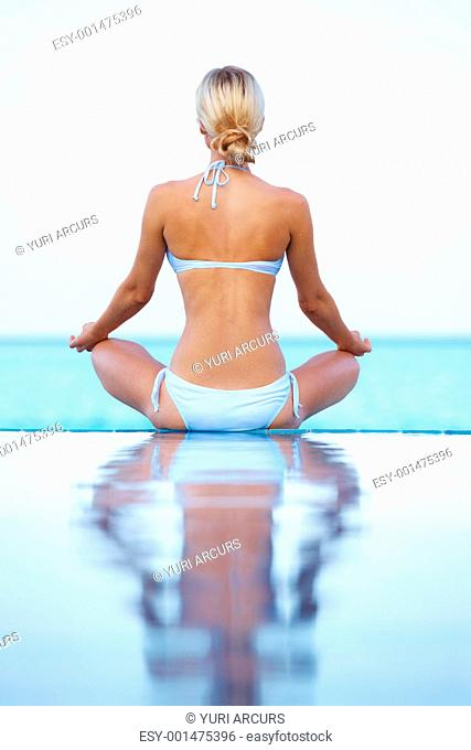 Rear view of young woman doing yoga on the pool by the sea