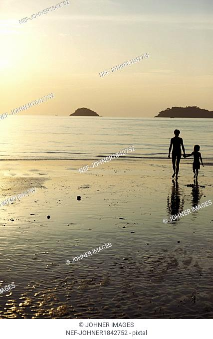 Mother with son walking on beach at dusk