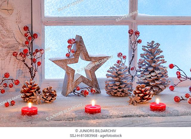 Christmas decoration: Three burning red tealights, stars, berries and cones in a window. Switzerland