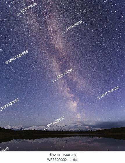 Starry sky over mountain and lake