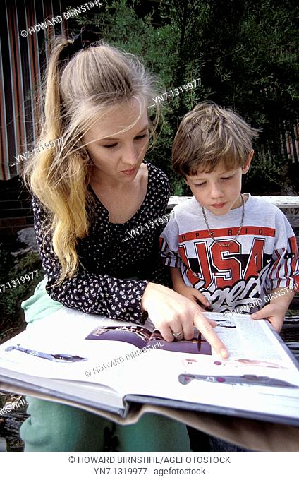 Mother and son sharing a book outdoors