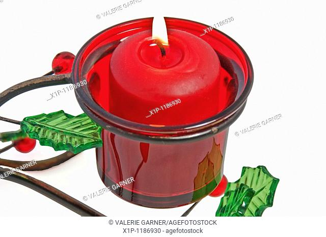 This red votive candle is lit and burning in a Christmas holder that is metal with glass holly leaves and berries, isolated on a white background