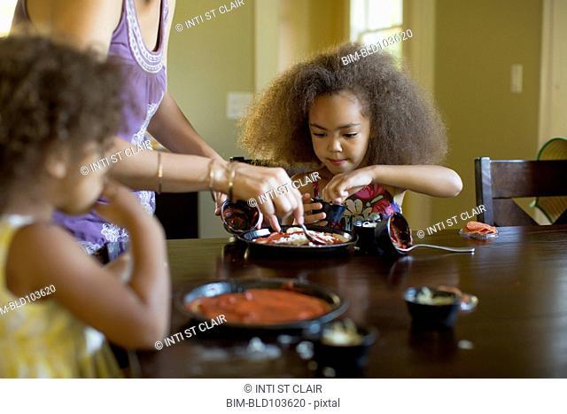 Mixed race girls eating dinner