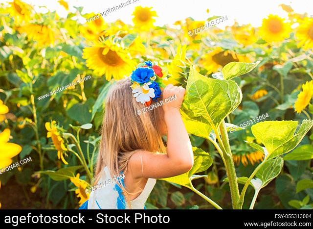 The little blonde girl is trying to hide among the wonderful sunflowers