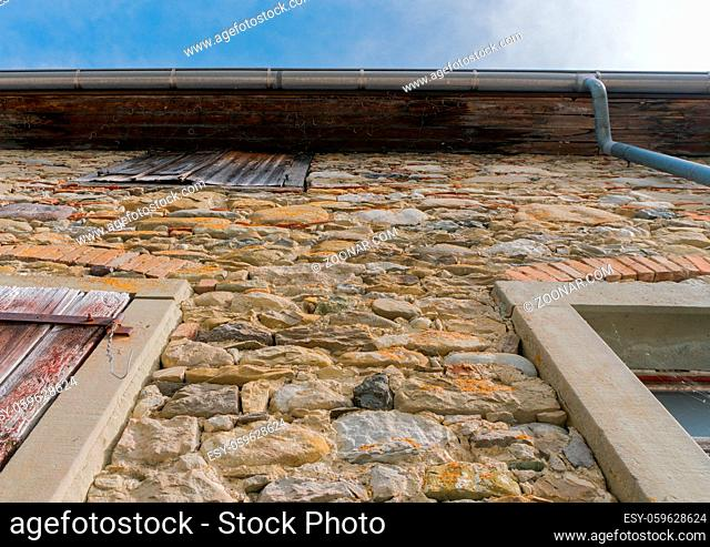 A low angle view of an old house facade built of massive stone with wooden shutters over the windows