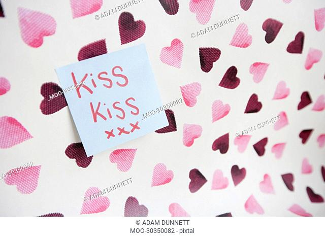 Close-up of sticky note with a message over heart shaped background