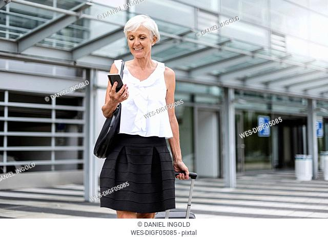 Smiling senior woman with baggage looking on cell phone