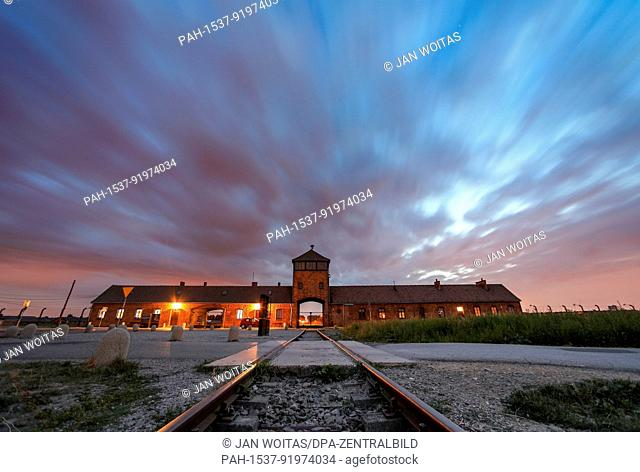 The gate of the former concentration camp Auschwitz-Birkenau can be seen in the evening in Oswiecim, Poland, 26 June 2017 (time exposure)