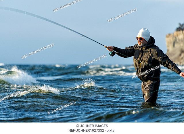 Man fishing in Baltic Sea, Gotland, Sweden