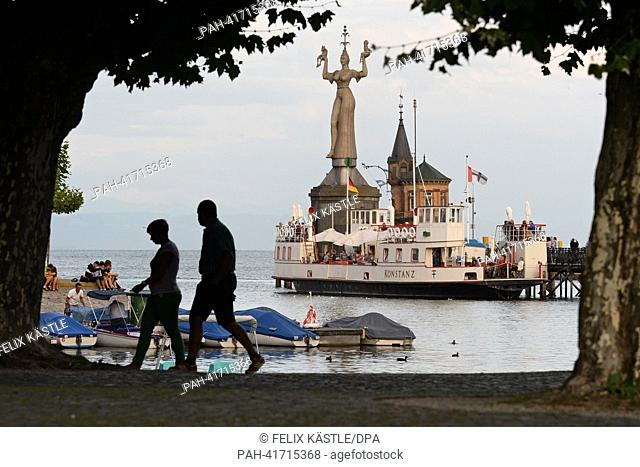 "Two people walk along the harbor promenade in front of the so-called """"Imperia"""", a statue at the entrance to the harbour, shortly before sunset in Konstanz"