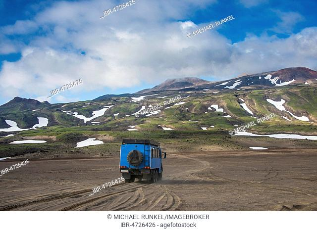 Truck driving through the lava sand, Gorely volcano, Kamchatka, Russia