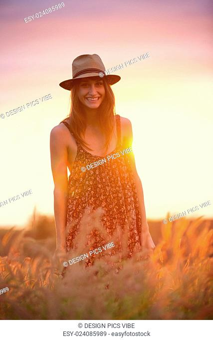 Beautiful happy woman in golden field at sunset, Carefree healthy lifestyle, Vibrant color, Backlit warm tones