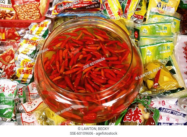 hot red peppers marinating in a glass jar