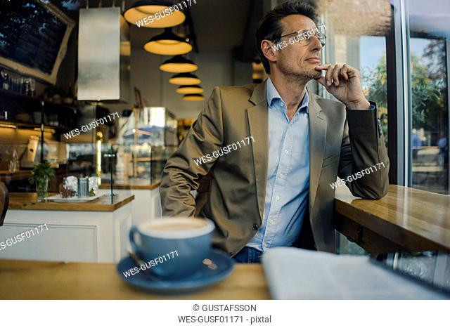Mature businessman sitting in coffee shop, smiling