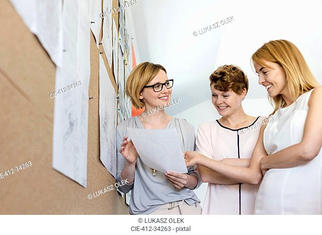 Smiling female designers reviewing proofs at bulletin board in office