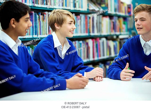 Female and male students discussing in college library