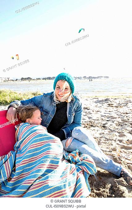 Mother and toddler girl in blanket on beach